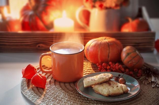 Oranje kopje thee en herfstdecor met pompoenen, bloemen en brandende kaarsen op tafel