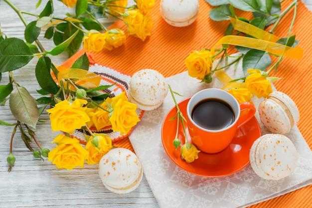 Oranje kopje zwarte koffie, gele rozen bloemen en zoete pastel franse bitterkoekjes op witte houten tafel. bovenaanzicht