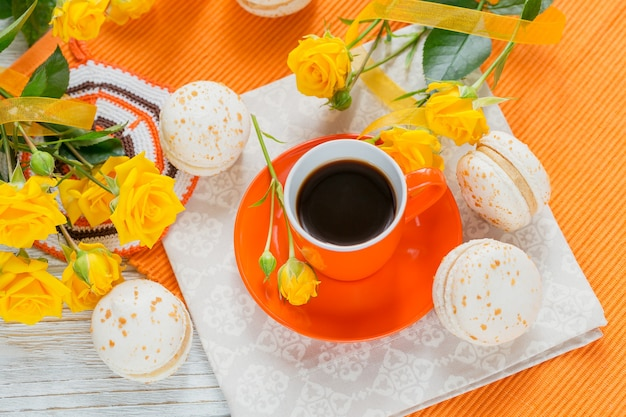 Oranje kopje zwarte koffie, gele rozen bloemen en zoete pastel franse bitterkoekjes op witte houten tafel. plat leggen