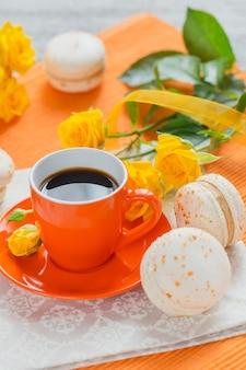 Oranje kopje zwarte koffie, gele rozen bloemen en zoete pastel franse bitterkoekjes op witte houten tafel
