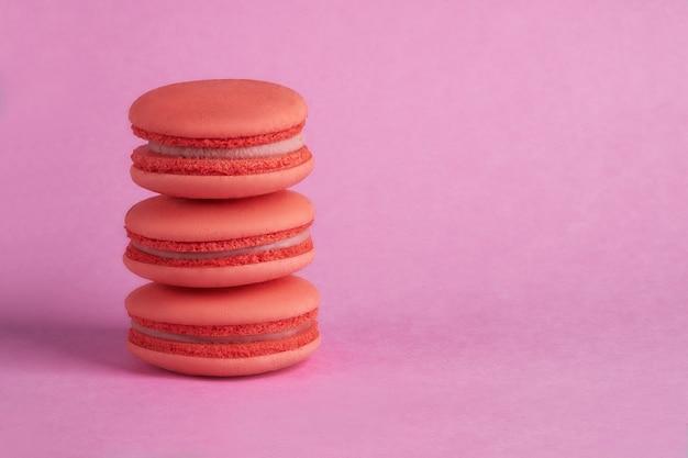Oranje macaron op een roze achtergrond