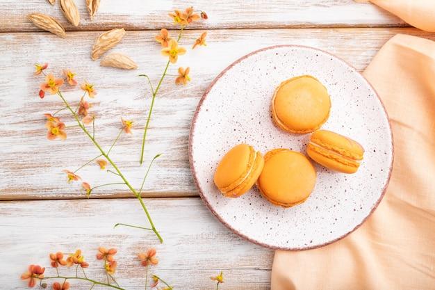 Oranje macarons of bitterkoekjes met een kopje abrikozensap