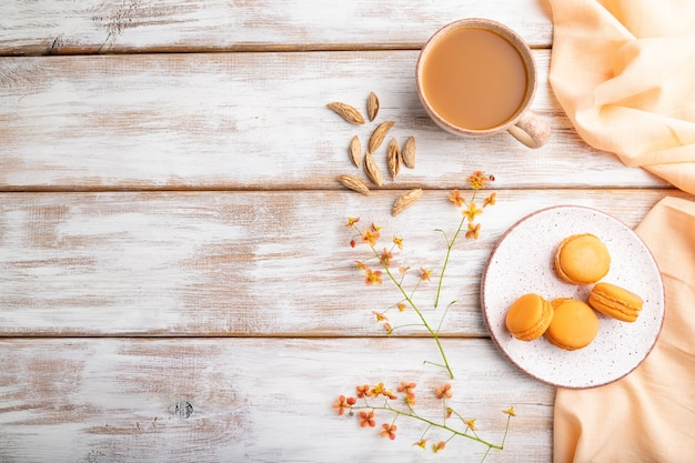 Oranje macarons of bitterkoekjes taarten met kopje abrikozensap op een witte houten tafel en oranje linnen textiel. bovenaanzicht, plat leggen, kopie ruimte.