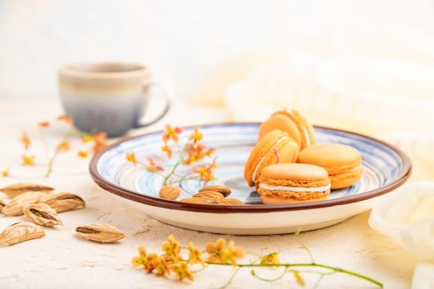 Oranje macarons of bitterkoekjes taarten met kopje koffie op een witte betonnen achtergrond en linnen textiel. zijaanzicht, close-up,