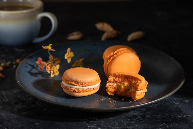 Oranje macarons of bitterkoekjes taarten met kopje koffie