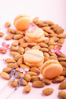 Oranje macarons of makaronscakes met amandelnoten op pastelkleur roze achtergrond