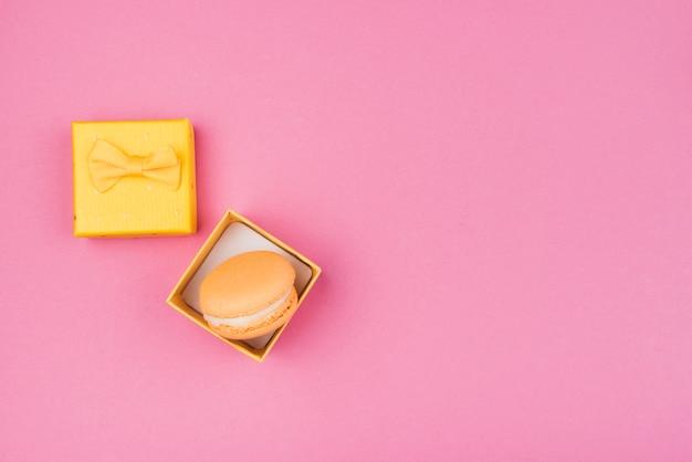 Oranje macaroon in gele geschenkdoos met kopie-ruimte