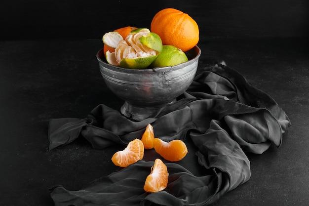 Oranje mandarijnen in een metalen beker op zwart oppervlak.