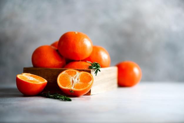 Oranje mandarijnen, mandarijnen, clementines, citrusvruchten met rozemarijn in houten kist