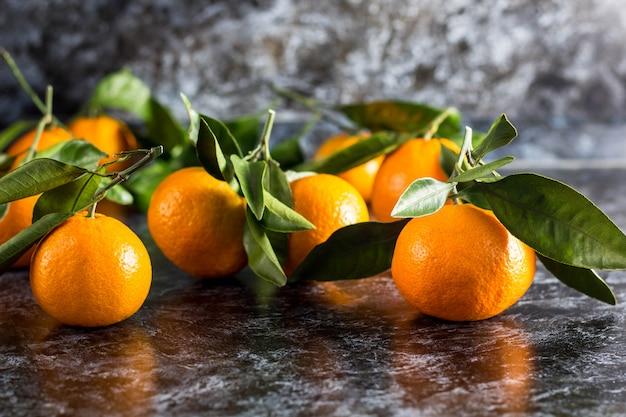 Oranje mandarijnen met groene bladeren op donkere achtergrond
