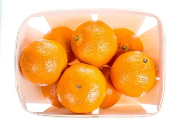 Oranje mandarijnenmandarin in een doos die op wit wordt geïsoleerd