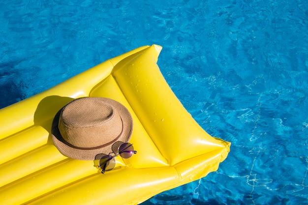Oranje matras in een zwembad met hoed en zonnebril