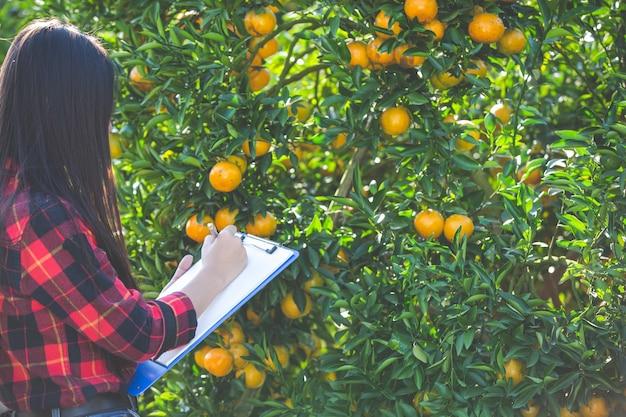 Oranje meisjeslandbouwer die lege vorm in hand houden.