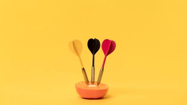 Oranje met darten op bureau