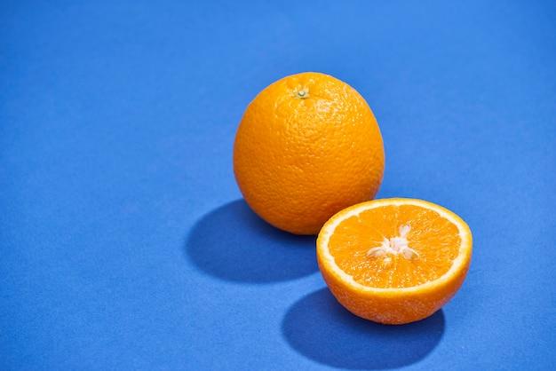 Oranje met de helft van sinaasappel geïsoleerd op de blauwe achtergrond