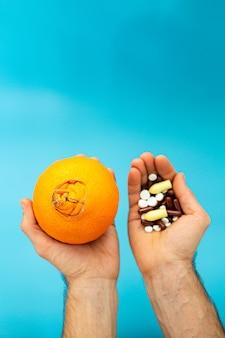 Oranje met een grote navel, pillen in handen op een blauwe achtergrond. aambei medicamenteuze behandeling concept.