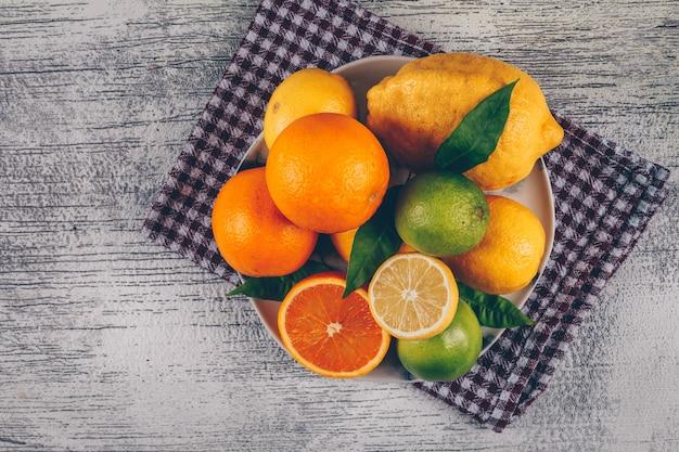 Oranje met groene en gele citroenen met segmenten in een plaat op doek en grijze houten achtergrond, bovenaanzicht.