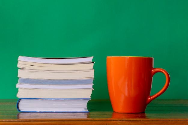 Oranje mok met stapel boeken op rustieke tafel en groene achtergrond