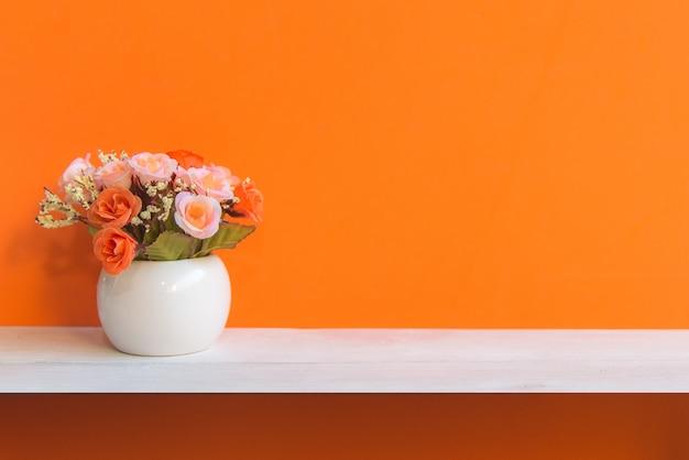 Oranje muur met bloemen op planken wit hout, exemplaarruimte voor tekst. stilleven concept