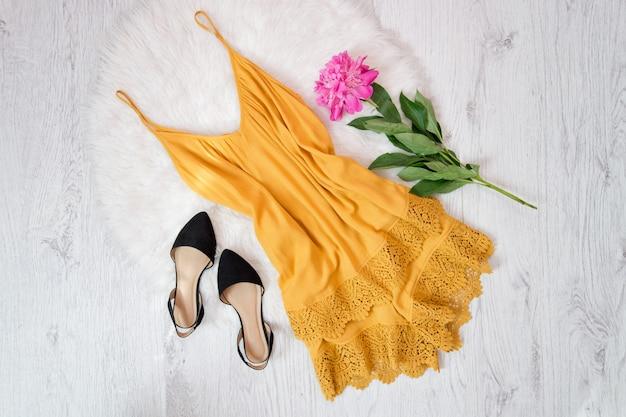 Oranje overall met kant en schoenen, pioenrozen op witte vacht. modieus concept