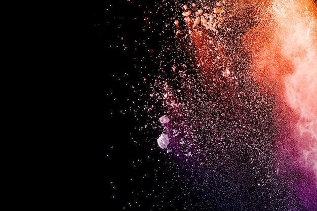 Oranje paarse poeder explosie op zwarte achtergrond.