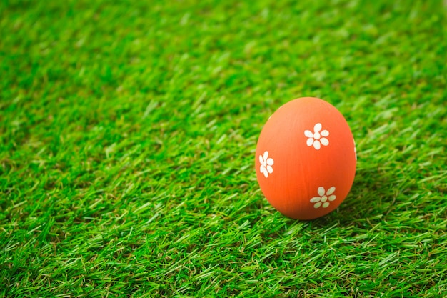 Oranje paasei op het groene gras.