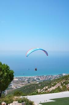Oranje paraglider vliegt over een bergdal op een zonnige zomerdag.