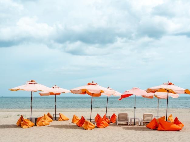 Oranje parasols en zitzak stoelen op het zandstrand op blauwe hemel