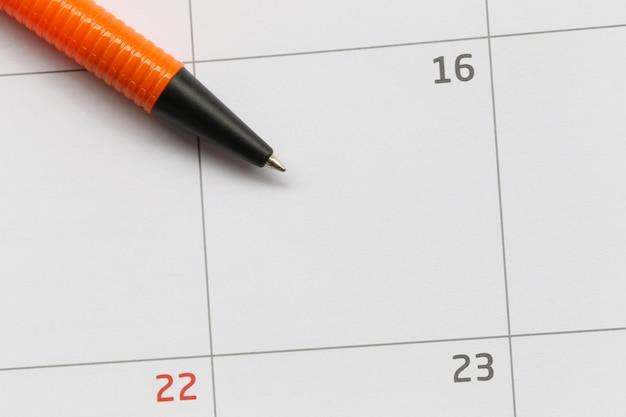 Oranje pen wordt op de zestiende dag op de kalender geplaatst en heeft kopieerruimte.