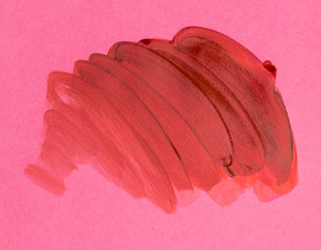 Oranje penseelstreek op roze achtergrond