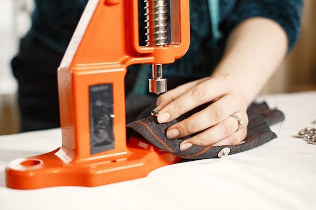 Oranje pers voor kleding. knopen op stof. vrouw met naaiende hulpmiddelen