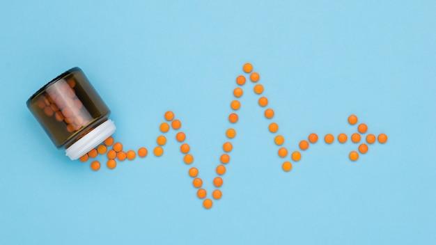Oranje pillen worden uit de fles gegoten in de vorm van een cardiogram