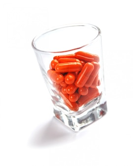 Oranje pillencapsules in glas op witte achtergrond