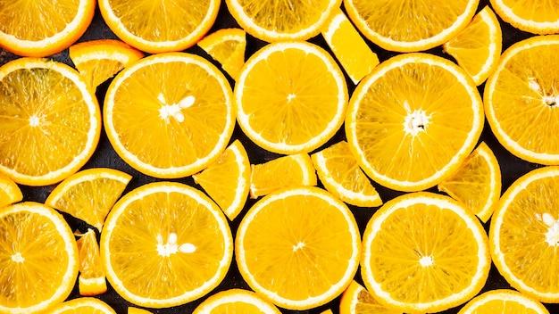 Oranje plakjes achtergrond. oranje fruitpatroon. voedselachtergrond met citrusvruchten. gezond voedselconcept. plat leggen. bovenaanzicht