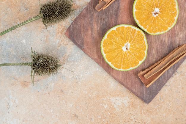 Oranje plakjes en kaneelstokjes op een houten bord.