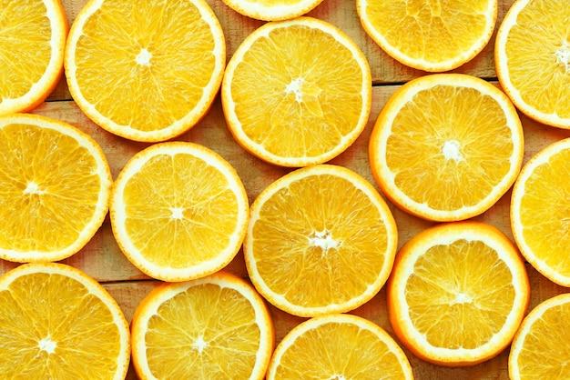 Oranje plakjes textuur achtergrond, vers oranje fruit oranje patroon op houten achtergrond