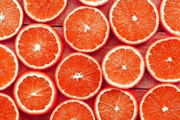 Oranje plakjes textuur achtergrond, vers oranje fruit oranje patroon op houten