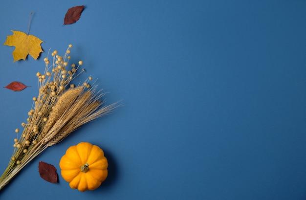 Oranje pompoen en herfstesdoorns op klassiek blauw.