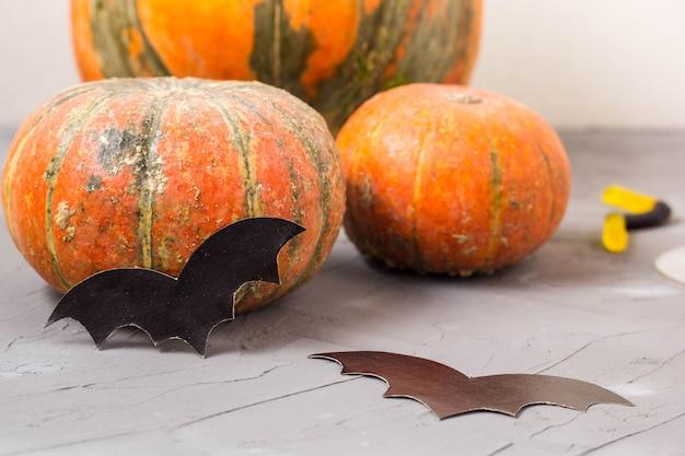 Oranje pompoen en papier vleermuizen op witte tafel