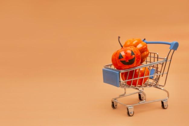 Oranje pompoenen in een kar en verspreide pompoenen op een beige achtergrond. platte lei over het onderwerp verkoop in halloween. kopieer ruimte