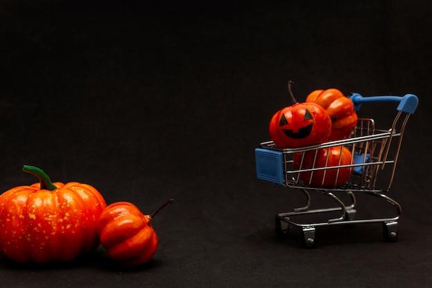 Oranje pompoenen in een kar en verspreide pompoenen op een zwarte achtergrond. platte lei over het onderwerp verkoop in halloween. kopieer ruimte
