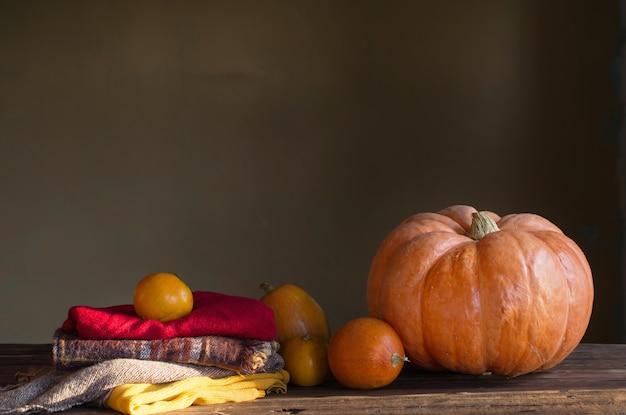 Oranje pompoenen met herfstbladeren op houten tafel
