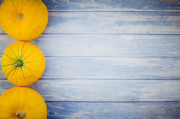 Oranje pompoenen op blauwe houten achtergrond