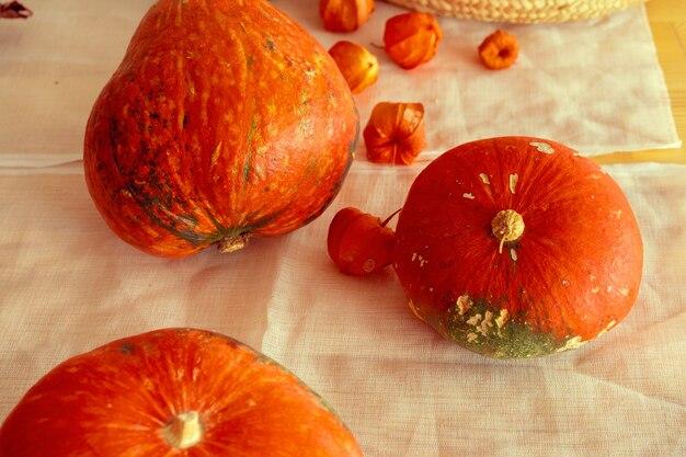 Oranje pompoenen op een tafel bedekt met linnen tafelkleed