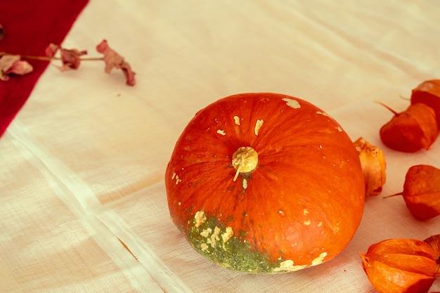Oranje pompoenen op een tafel bedekt met linnen tafellaken