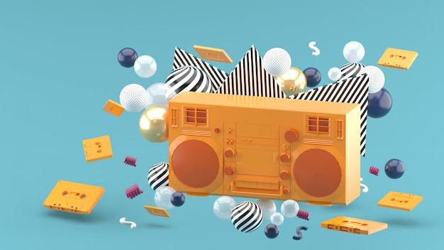 Oranje radio temidden van kleurrijke ballen op blauw. 3d render