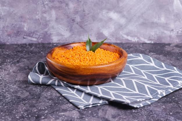 Oranje rauwe linzen voor een goede voeding en gezondheid in een houten plaat op een grijze achtergrond
