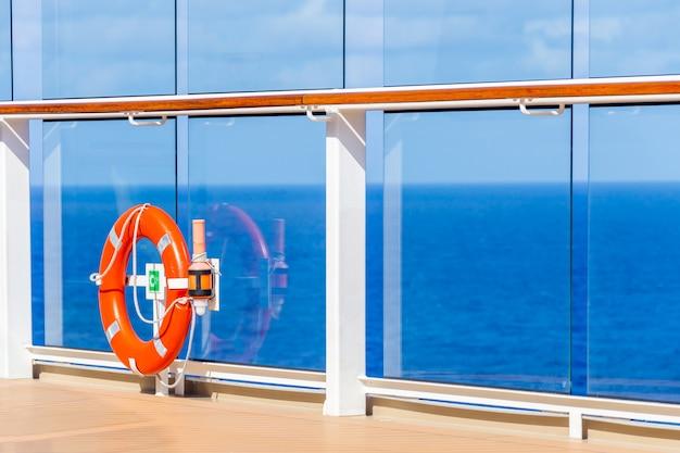 Oranje reddingsboei op een dek van cruiseschip met oceaan