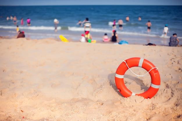 Oranje reddingsboei op voorgrond blauwe heldere hemel zee en mensen apparatuur voor redding levensreddend