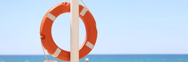 Oranje reddingsboei weegt op mast tegen achtergrond van zee